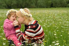 Fun on the spring meadow. Woman and baby girl having fun on the spring meadow full of daisies royalty free stock images