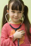 Fun with stethoscope. Girl have fun with stethoscope royalty free stock photo