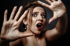 Scared woman screaming. Fun stressed scared girl in dark looking at camera screaming Royalty Free Stock Image