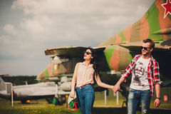 Fun and stylish couple walking near the aircraft Stock Images