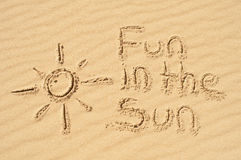 Fun in the Sun written in the Sand. A picture of the sun and the words fun in the sun drawn in the sand Royalty Free Stock Photo