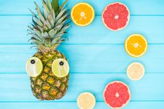 Fun summer fruit still life with a pineapple. With sliced lemon eyes and assorted halved fresh citrus on a blue wooden background with copy space royalty free stock photo