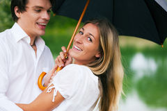 Fun in the summer rain. Couple (man and woman) at a lake in the summer rain with an umbrella, laughing and having fun despite of the bad weather Stock Photography