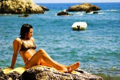 Fun in the Sun. Beautiful model having fun in the sun, reclining on a rock with waves crashing in Stock Photo