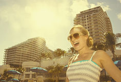 Fun in the Sun. A young woman laughing and screaming with delight while having fun in the sun at a tropical resort. Vintage feel Stock Photo