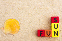 Fun in the Sun. Letters spelling fun and sun on sand with copy space Stock Image