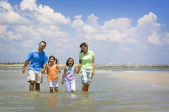 Fun in the sun. Family on vacation walking on a beach Royalty Free Stock Photos