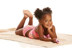 Fun in the sun. Adorable little girl laying out on a beach towel.  Isolated on white Royalty Free Stock Photos