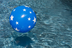 Fun in the Sun. Blue beach ball with white stars floating in the blue waters of a swimming pool on a sunny day Royalty Free Stock Image
