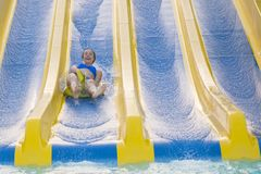 Fun in the sun-pretty girl in bikini comes down water chute in to swimming pool. Beautiful girl riding a water slide. happy woman. Going down on the rubber ring stock images
