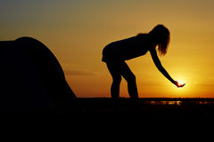 Fun with the sun. Silhouette of a woman having fun near a camping tent at sunset Royalty Free Stock Photography