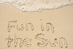 Fun in the Sun Written in Sand on Beach Stock Photo