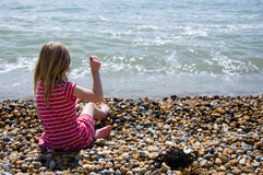 Fun in the sun. Young girl sitting down throwing pebbles in the sea on a beautiful sunny day Royalty Free Stock Images