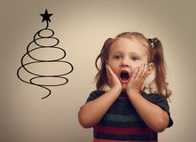Fun surprising happy child girl looking on christmas fur tree Royalty Free Stock Images