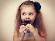 Fun surprising kid girl eating dark chocolate. Vintage closeup. Portrait stock photos