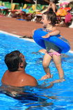 Fun in swimming pool. Father play with her daughter in swimming pool Royalty Free Stock Photo
