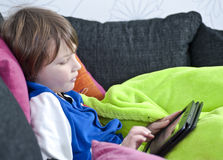 Fun with tablet. Young boy in sofa playing with a tablet Stock Image