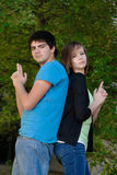 Fun Teens. Two teens having fun and pretending to hold guns while standing back to back Royalty Free Stock Images