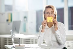 Fun with teeth. Mid-aged employee with drawn smile and long teeth on notepaper by her mouth looking at camera Stock Images