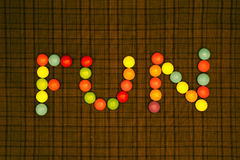 Fun. Text Fun made like composition of color rounds on checked fabric background stock photo