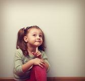Fun thinking kid girl sitting in pink jeans and looking up Royalty Free Stock Photography