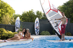 Fun time by the pool. Windsurfer in a pool with two women tanning Stock Photo