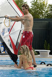 Fun time in the pool. Windsurfer in a pool with blond bombshell Royalty Free Stock Photos