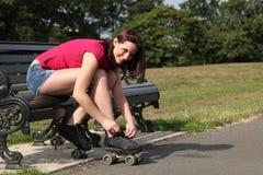 Fun time in sun beautiful girl putting on skates Royalty Free Stock Photos
