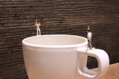 The fun of the tiny  golfers play on mug Royalty Free Stock Image