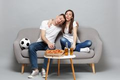 Fun tired couple woman man football fans in white t-shirt cheer up support favorite team sleeping, showing tongue. Fun tired couple women men football fans in stock photography