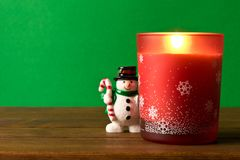 Fun toy snowman and a Christmas candle on a wooden table. The co royalty free stock photo