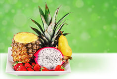 Fun tropical fruit mix. Welcome to the tropics: tropical fresh fruits served in a white plate on fun green background Royalty Free Stock Images