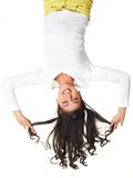 Fun upside down. Vertical portrait of a cheerful funny girl hanging upside down and playing with her hair royalty free stock photo