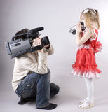 Fun video shooting. Professional cameraman and little girl with home video camera shooting one another Stock Photos