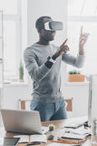 Fun with virtual reality headset. Handsome young African man in VR headset gesturing and smiling while standing in creative office Stock Image