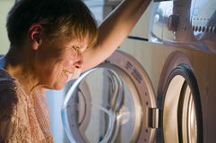 Fun for washer. Head-and-shoulder view looking a mature woman in front of the open door of the washing machine squatting and in the washing machine Stock Photography