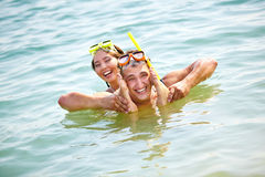 Fun in water. Hilarious couple having fun in water, guy holding his girlfriend's feet by his face Stock Photos