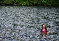 Fun in the Water. Young girl swimming in a lake. Image shows open water with trees in the background Royalty Free Stock Photography