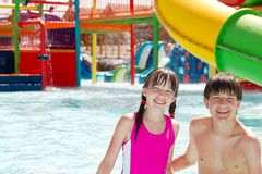 Fun at the waterpark. Brother and sister smiling as they play and have fun together in a swimming pool at an outdoor waterpark Stock Photos
