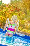 Happy healthy child in swimwear standing in swimming pool. Fun weekend alfresco. happy healthy child in colorful swimwear standing in the swimming pool Stock Photo