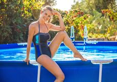 Happy active woman in blue swimwear sitting on swimming pool stock image
