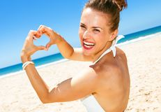 Happy modern woman on seashore showing heart shaped hands Stock Photo