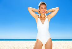 Happy modern woman in swimsuit on seacoast dressing swimsuit. Fun on white sand. happy modern woman in swimsuit on the seacoast dressing a swimsuit Royalty Free Stock Photos