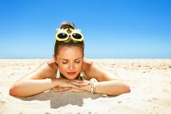 Portrait of relaxed young woman in beachwear laying on seashore royalty free stock photos