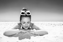 Portrait of relaxed young woman in beachwear laying on seashore royalty free stock photography