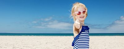 Girl in striped swimsuit on a white beach showing thumbs up Royalty Free Stock Images