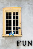 The Fun Window. Yellow window with two small flags of Quebec City with the word FUN on the wall Stock Photos