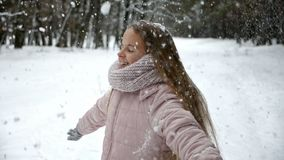 Fun in winter forest - girl spinning under falling hoarfrost stock footage