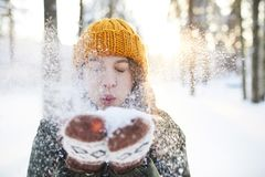 Fun in Winter Park. Portrait of happy young woman playing with snow in winter, blowing snowflakes to camera, copy space royalty free stock photos