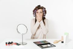 Fun woman with curlers cover mouth with hands, sitting at table applying makeup with set facial decorative cosmetics royalty free stock images